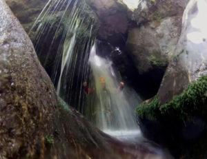 persona_con_neopreno_bajo_el_agua_de_una_cascada_de_barranco_por_Picos_de_Europa_Valdeón