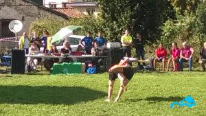 Lucha_leonesa_en_fiestas_de_corona_2_luchadores_caen_al_prado_agarrados_de_fondo_público_mirando_día_soleado_Valle_de_Valdeón