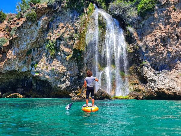 hombre sobre tabla paddelsurf frente cascada Maro Cerro-Gordo en Nerja Malaga